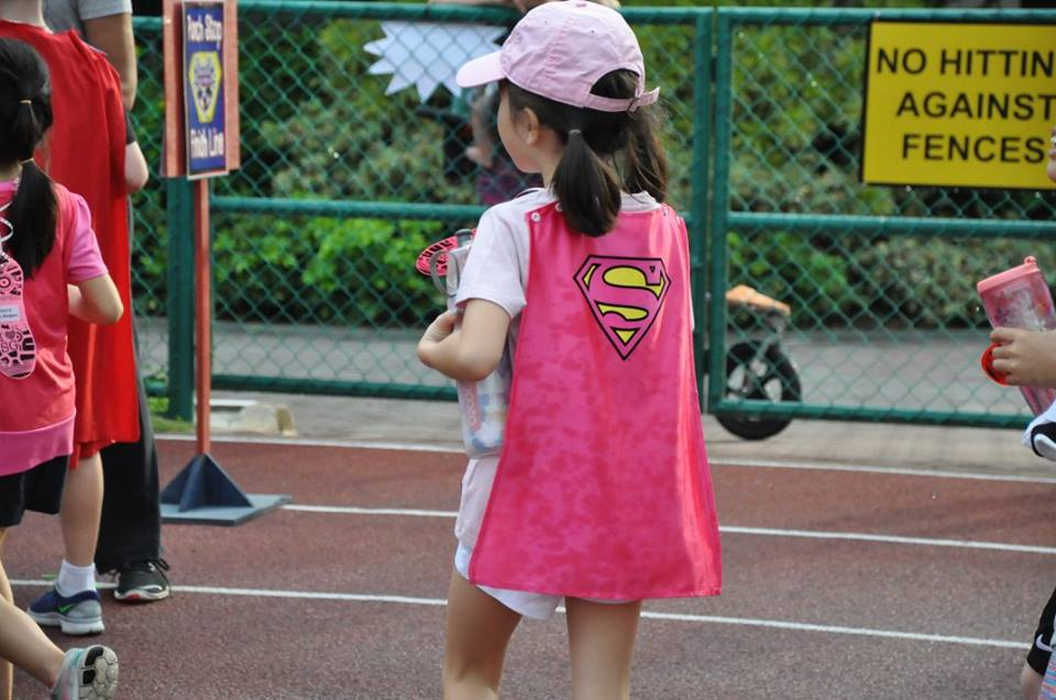 young student with superhero cape